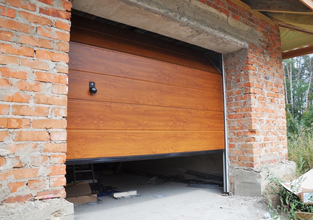 Installing garage door in new brick house construction.